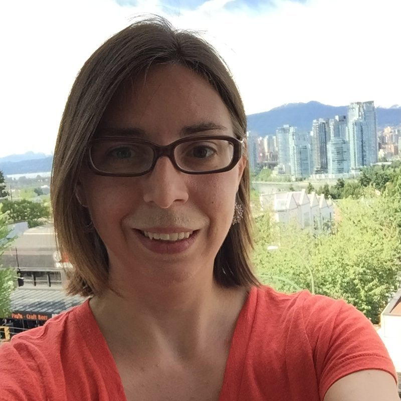 Image of a woman in glasses smiling in front of a lovely view