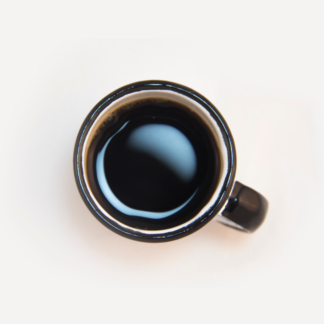 Image of a cup of black coffee, taken from above. The cup is dark brown against a cream background.